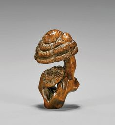 CARVED BOXWOOD NETSUKE: Mushrooms Antique 19th century Japanese carved boxwood netsuke; depicting a taller mushroom cap over a smaller one at the base of the stalk; signed