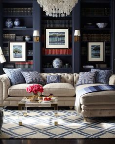 Sophisticated living room. The walls are a very cool shade of blue. For the dining room? Like the pillows and rug too.