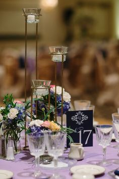 Elegant centerpiece idea - raised candle votives and colorful, fresh flowers in glass vases {The Grays Photography}
