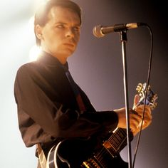 [Color photo of Gary Numan playing a guitar on stage while side-eyeing] Phil Collins, Gary Numan, Lisa, Music And Movement, Post Punk, Cool Guitar, Pop Rocks, Old Boys, My Favorite Music