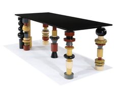 "Ettore Sottsass  Golden Eye table  Executed in India 1984  Plychromed and turned wood with marble top  Custom  31"" x 76"" x 33.5"""