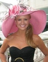 Nancy O'Dell wearing a big beautiful pink hat! One of the Churchill Downs steeples in the background.