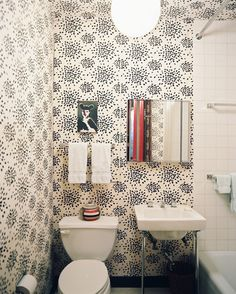 Black-and-white-patterned wallpaper and square white tile in a bathroom -- could use wallpaper on top half?