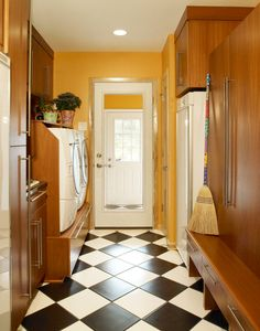 Laundry room with black and white checkered tiles, part of a home whole remodel by B&E General Contractors in Glendale, WI