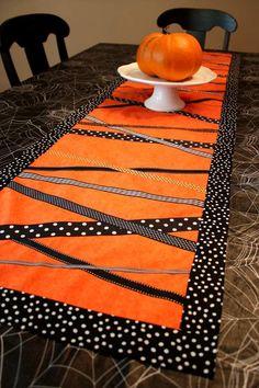 chemin de table en orange et noir à pois blancs et une citrouille orange