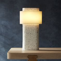 Shop shiro table lamp.   Drawing inspiration from Japanese stone lanterns and fence posts, designer Ross Cassidy's sculptural table lamp shines with understated elegance.  Sculptural warm linen shade hovers atop white polyresin/stone base.