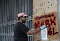 A worker cleans graffiti outside the central Bank of Greece building in Athens, Greece, July 7, 2015.