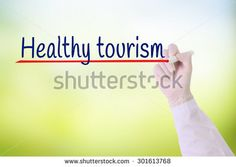 Doctor hand with Glove writing Health tourism over green blurred background