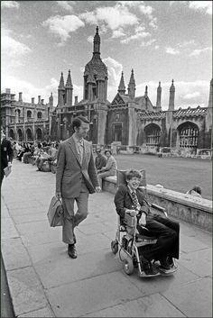 Ian Berry  England. Cambridge. Professor Stephen Hawking in his wheelchair in front of university buildings. 1977