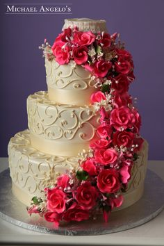 Hot Pink Roses #17Floral This three-tier fondant cake is wrapped in an ivory satin ribbon and decorated with an ornate swirl. The gum paste roses cascade down the one side.