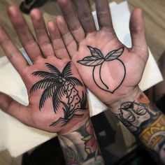 Black ink palm tree and peach done on the palms of guy's hands.