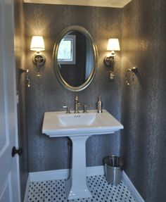 """1/2 bathroom with 32"""" pedestal sink, wall sconces, wall paper and basket weave marble floor."""
