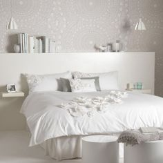 White and lace bedroom with oversized headboard and lace patterned wallpaper