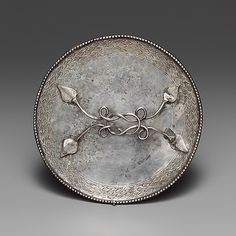 Imperial Roman silver mirror, c400. This type of mirror with a horizontal handle originated in the Roman world during the first century B.C. In this example, the classical origins are clear in the leaf-shaped attachments of the handle, the Herakles knot, and the wreath around the circumference of the disk. (Metropolitan Museum of Art)
