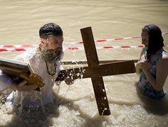 Orthodox Christians immerse themselves in the Jordan River at a baptism ceremony near the West Bank town of Jericho.  The site is traditionally believed by many to be the place where Jesus was baptized.