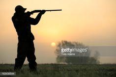Stock Photo : Silhouette of a hunter aiming his shotgun