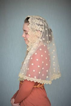 This lovely chapel veil is made of a stunningly beautiful, vintage gold lace. The color is the palest of golds, with an intricate embroidered pattern featuring roses and scallops. A pale gold, embroidered lace trim graces the edge. This mantilla is a rounded, D-shape and hits below the