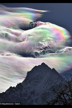 Rainbow cloud above Mt. Everest. This rainbow effect is created when tiny ice crystals in the water vapor of the clouds reflect the sun light.
