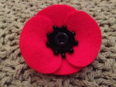 Handmade Felt Poppy Brooch with bead detail. Each brooch is hand cut from red and black felt with a button centre and bead detailing. Each brooch is approx. 6cm wide and had a clasp attached to the back. All items are handmade by Lovelies. If you have any questions please feel free to get in touch x