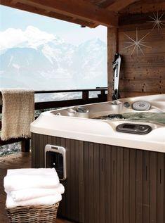 Jacuzzi installé sur la terrasse couverte de ce chalet en bois alpin