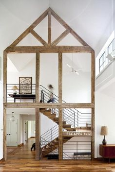 Staircase up and down. Exposed beams. White Walls. Modern railing.