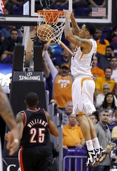 Phoenix Suns' Gerald Green dunks as Portland Trail Blazers' Mo Williams (25) watches during the first half in an NBA basketball game Wednesday, Oct. 30, 2013, in Phoenix. (AP Photo/Ross D. Franklin)