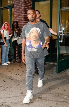 Peace: Kanye wore a Tshirt with the image of late rapper Tupac Shakur for the family's day out
