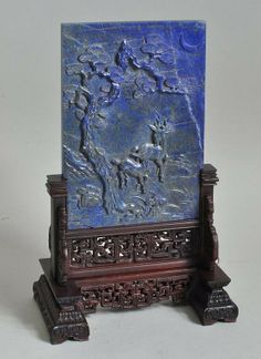 Carved lapis lazuli table screen, the rectangular plaque carved with deer and pine tree in relief, on an elaborately carved and reticulated wood stand, possibly 18th century.