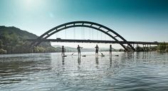 A flotilla of stand-up paddlers will glide 21 miles down Lake Austin on June 4, raising awareness about the importance of mental health for people coping with cancer. Photo from the 2011 Dam That Cancer event by Randal Ford.