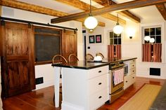 Exposed beams and sliding barn doors maintain the historical integrity of this kitchen while creating a functional space to meet the needs of a growing family. | thisoldhouse.com