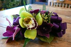 Orchid wrist corsage with green cymbidiums and purple dendrobiums.