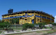 Estádio La Bombonera, Buenos Aires, Argentina, propiedad del Club Atletico Boca Juniors. Fue inaugurado el 25 de mayo de 1940. Al construir un estadio grande en un predio muy reducido, fue necesario edificar las bandejas muy juntas una sobre otra, y las superiores se encuentran muy adelantadas con respecto a las inferiores, creando una pendiente pronunciada y poco común. Este diseño atrevido crea, una atmósfera compacta y vibrante, que derivó en la frase popular «la Bombonera no tiembla…
