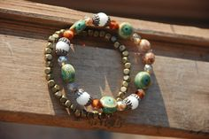 "Mermaid Treasures $6 This pair of bracelets are made with a mix of ceramic, Czech, Swarvoski and antiqued brass beads.  Fits 6""-7.5"" wrists (size small). Stretchy band.  *Keep out of reach from small children. Choking hazard.*"