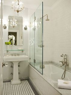 White subway tile on the wall and marble on the tub surround. Black border on floor tile. Morris Adjmi Architects