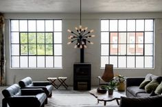 Black and White Urban Living Room with Black Armchairs and Gray Sectional Black Armchair, Apartment Lighting, Black And White Living Room, Urban Apartment, Grey Sectional, Outdoor Sconces, Grey Kitchens, Loft Design, Living Room Remodel