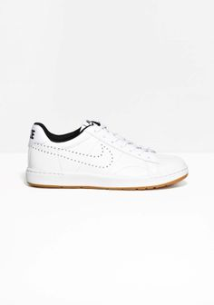 NIKE A classic tennis silhouette highlighted by premium quality leather and understated monochrome design.