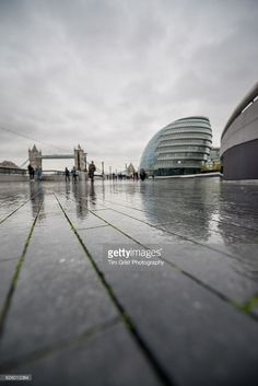 A low angle view of City Hall at The More London business district with Tower Bridge in the background.
