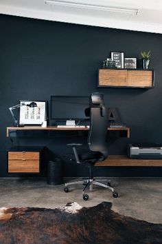 Home office area with black office chair at console desk and small cabinet modules mounted on black wall