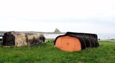 The use of abandoned boats as sheds is an East Coast of England tradition. These upturned boatsheds are found at the harbour on Lindisfarne, Northumberland, are still used by local fishermen.  The boat sheds at the castle first appeared when Edwin Lutyens restored Lindisfarne castle for Edward Hudson at the turn of the last century. The Spanish architect Enric Miralles used Lutyens' upturned herring busses as an inspiration