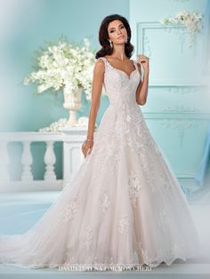 Sleeveless Tulle over satin full A-line gown with hand-beaded re-embroidered lace appliques curved sweetheart neckline, dropped waist, illusion back