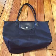 Brown longchamp le pliage tote small Nice tote by longchamp! This one does not fold as it does not have a snap in the back. It has some stains but I haven't tried to clean it. Please see pics for wear. Leathee has some wrinkles. Longchamp Bags Totes