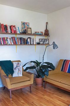Reading nook with DIY custom shelving. The mid-century couch and chair are yet another Kijiji score. Giraffe cushion – Zone.