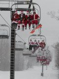 Skiers and Snowboarders Dressed as Santa Claus Ride up the Ski Lift Photographic Print