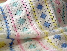 A lovely soft and colorful baby afghan perfect for the nursery. White surrounding small granny squares of blue, pink, mint green, and yellow with