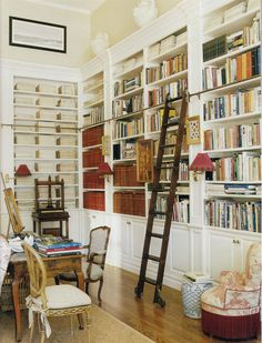 A corner of the East Hampton retreat of interior decorator Charlotte Moss. A rolling ladder accesses the higher parts of the white-painted and molding-crowned shelves. The brown volume sets are bound interior design magazines – a useful way to corral large magazine collections.