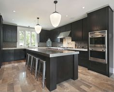 Dark cabinets, grey countertops and light wood floors