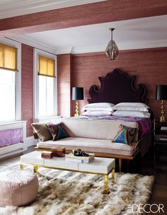 In Jackie Astier's master bedroom, the custom-made headboard is upholstered in an Osborne & Little velvet, and the bed is dressed with Sferra linens and a vintage suzani; the cocktail table, bedside tables, and rug are by Amir Khamneipur, the 1960s settee is Danish, the shades are from Pearl River, and the walls are covered in a grass cloth by Phillip Jeffries.   - ELLEDecor.com
