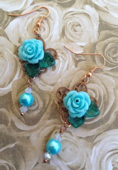 Blue Rose Earrings .. Roses are mounted on a copper stamping with glass leaves .. hanging from bottom are pearls with 4mm crystals ..  FOR SALE .. $15.00 .. SOLD .. https://www.facebook.com/JewelsByJann