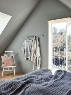 Home Remodel Before And After A collection of robes hang from neat wooden pegs painted the same colour as the bedroom walls, Jotun Pale Linden, in this Swedish island home. Bedroom Green, Bedroom Wall, Plywood Interior, Minimal Bedroom, Swedish House, Nordic Interior, Open Plan Living, Soft Colors, Colours