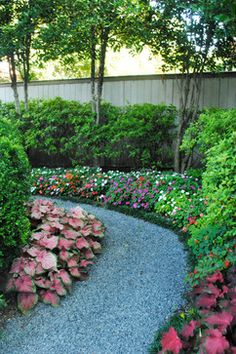 Impatiens, coleus line this walkway of stone pebbles. good for a shady sideyard